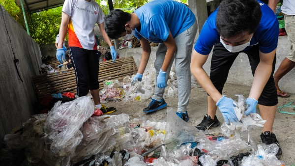 Volunteer sorting through waste at Les Bali